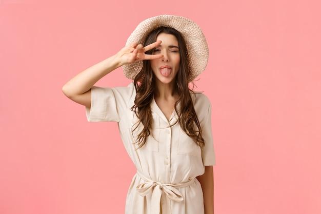 陽気で美しい若いブルネットの女性は素敵な一日を楽しんで、恍惚と大喜びを感じて、目の近くにピースサインを見せて、目を閉じ、舌を喜んで、ピンクの壁に立っています。
