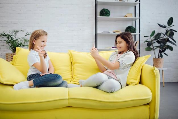 명랑하고 감정적 인 청소년 노란색 소파에 앉아있다. 전화 카메라에 그녀의 친구의 갈색 머리 소녀 복용 사진. 왼쪽 포즈와 미소에 십 대입니다.
