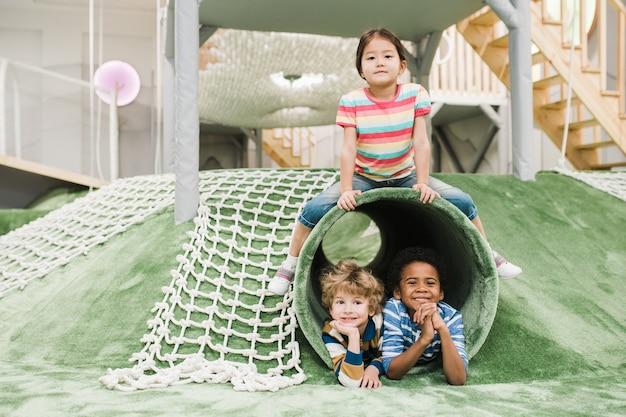 Веселые и дружелюбные межкультурные маленькие дети веселятся вместе на игровой площадке современного развлекательного центра.
