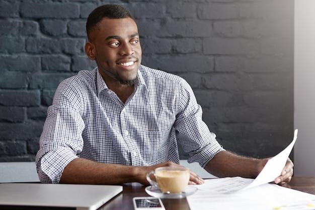 幸せそうに見えてフォーマルな服装で陽気でハンサムな若いアフリカオフィス男