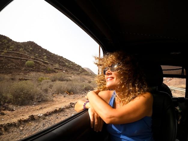 車の乗客のように旅行を楽しんでいる陽気で幸せな大人の美しい女性