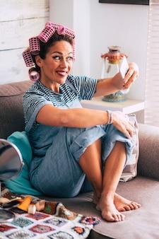 陽気で幸せな大人の白人の美しい女性は、友人との自撮り写真の共有とcovid-19検疫ロックダウン緊急時に自宅での電話を撮ります