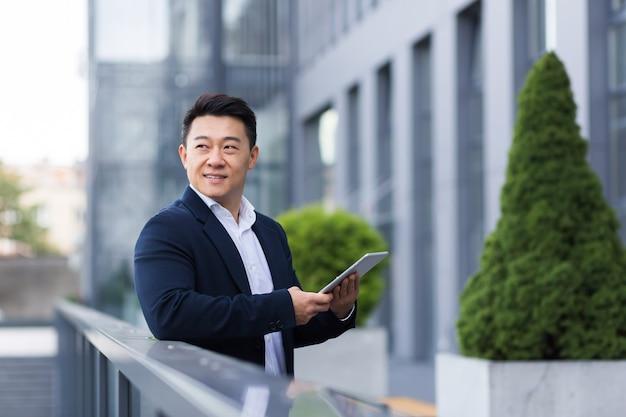 명랑하고 행복한 아시아 보스는 비즈니스 정장을 입은 현대 사무실 남성 사업가 근처 태블릿에서 뉴스를 읽습니다.