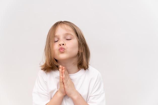 散髪クワッドを持つ陽気で幸せな少女は、白い背景で彼女の前に彼の折り畳まれた手を保持します。幸せな子供時代。子供のためのビタミンと薬。願い事をして夢を信じる