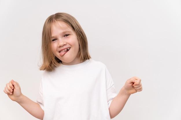 Веселая и счастливая маленькая девочка с четырехъядерной стрижкой с высунутым языком на белом фоне. счастливое детство. витамины и лекарства для ребенка.