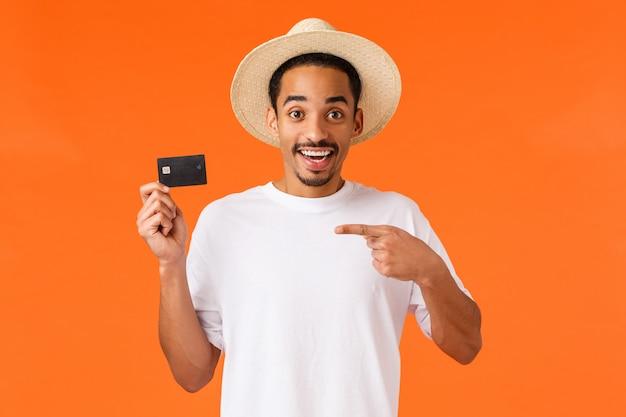 陽気で幸せな、笑顔のアフリカ系アメリカ人の男が素晴らしい新しい銀行に口座を開設し、クレジットカードを指して、笑顔で満足して、顧客サービスのように、オレンジ色に立っています。