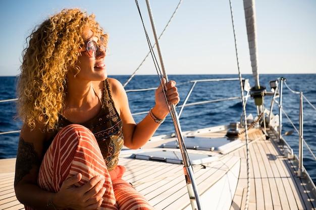 彼女の仕事から小さな休暇を取る海を旅するボートやヨットに乗って陽気で幸せな女性-コンセプト。夏休みのアウトドアレジャー。自由にそして喜びをもってセーリング活動