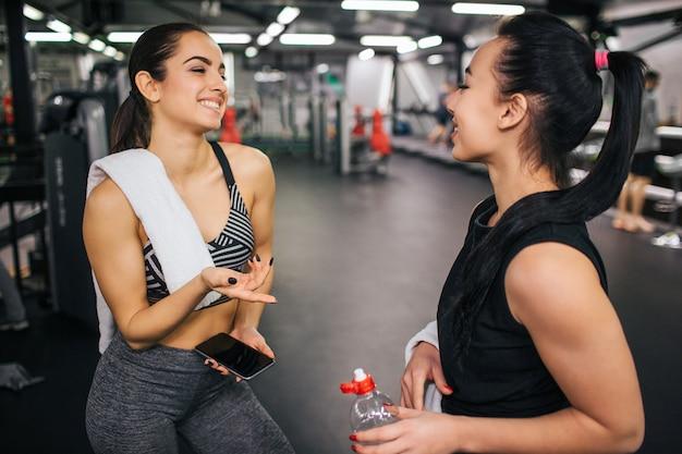 쾌활하고 행복 젊은 여자가 그녀의 아시아 친구에게 회담.
