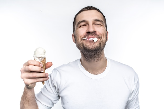 Веселый и жизнерадостный мужчина ест мороженое не очень аккуратно, но с большим удовольствием.