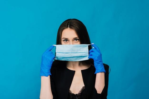 青の背景に防護マスクと手袋で遊んで陽気でうれしそうな若い女性。クローズアップの肖像画。コロナウイルス検疫の終わり。