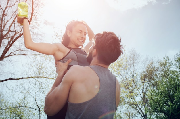발랄하고 아름다운 커플의 멋진 사진. 남자는 그의 여자 친구를 손에 들고 그녀를 보고 있습니다. 그녀는 물 한 병을 들고 웃고 있습니다. 그들은 행복해 보인다