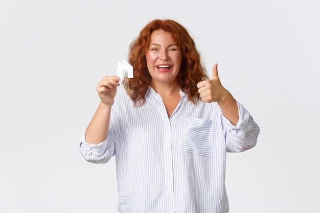 陽気で喜んでいる中年の赤毛の女性が家のカードと親指を立てて