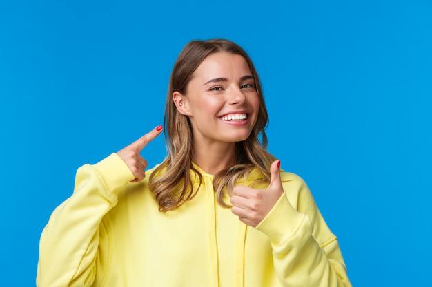 명랑하고 기쁘게 생각하고 만족스러운 잘 생긴 유럽 여성이 피어싱 된 귀를 가리키고 웃고 기쁘게 생각합니다. 새 보석처럼 엄지 손가락을 보여줍니다.
