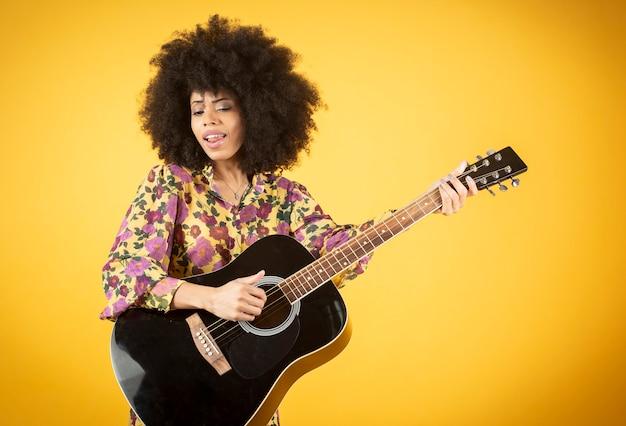陽気で人気のあるかわいい女の子がギターを弾くアフリカのウェーブのかかった髪を混ぜた