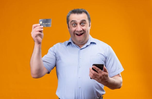 陽気で肯定的な中年男性が携帯電話を押しながら立っている間クレジットカードを示す青い剥奪シャツを着ています。