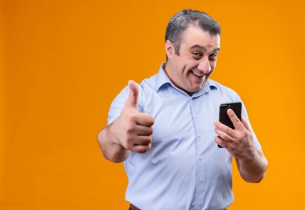 Веселый и позитивный мужчина среднего возраста в синей полосатой рубашке держит мобильный телефон и показывает палец вверх, стоя