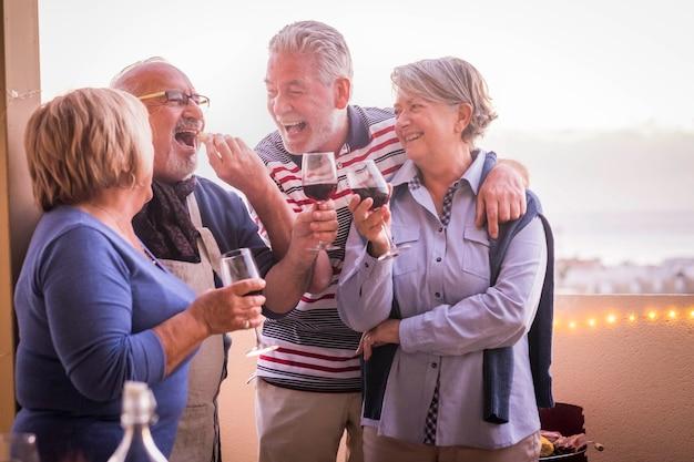 쾌활하고 웃는 성인 그룹은 테라스에서 야외 칵테일 레저 활동을 즐길 수 있습니다. 여름 시즌과 웃음. 우정에서 함께 재미있는 라이프 스타일에 아름다운 은퇴 한 사람들. 셀레 프리미엄 사진