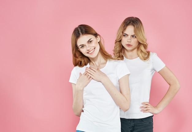 ピンクの壁に白いtシャツを着た陽気で動揺した女性