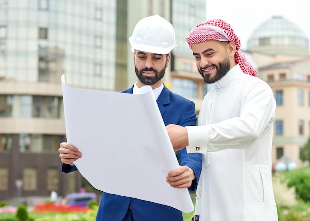 彼の建築家といくつかの青写真を行っている陽気なアラブのビジネスマン