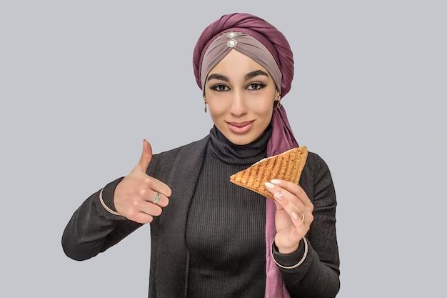 陽気なアラビアの女性が立って、別のものと大きな親指を現す