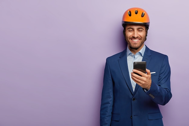 陽気な建築家はオレンジ色のヘルメット、フォーマルなスーツを着て、仕事の休憩中に暇があり、スマートフォンでメッセージを受け取り、給料を喜んで受け取ります