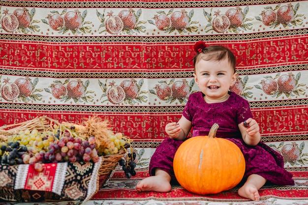カラフルな背景の前に座って笑っている陽気なアルメニアの赤ちゃん