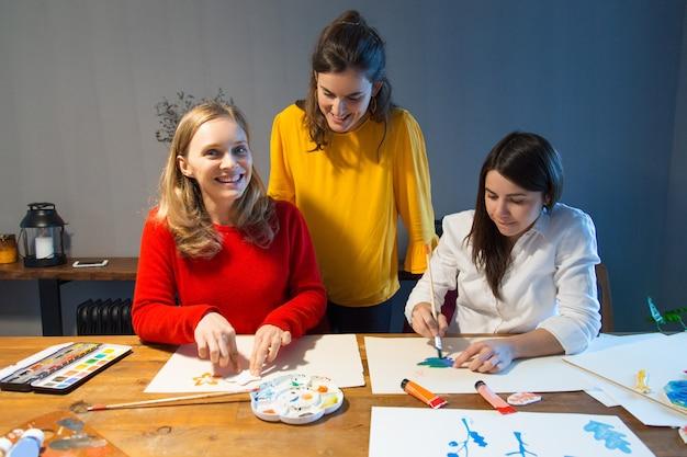 Веселый учитель рисования и ученики наслаждаются уроком рисования