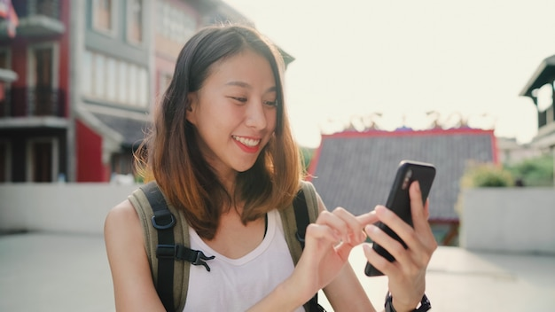 Cheerful asian backpacker blogger woman using smartphone for direction and looking on location map