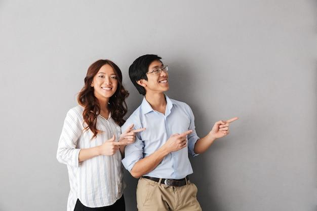 Веселая азиатская деловая пара стоит изолированно, указывая пальцами