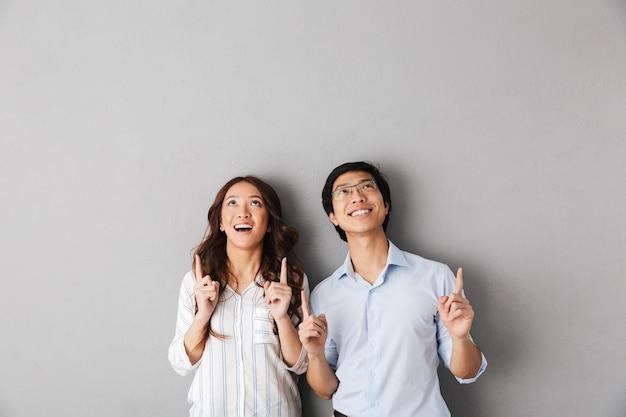 Веселая азиатская деловая пара стоя изолированно, указывая пальцами вверх