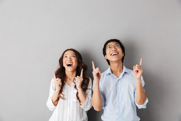 Cheerful asian business couple standing isolated, pointing fingers up