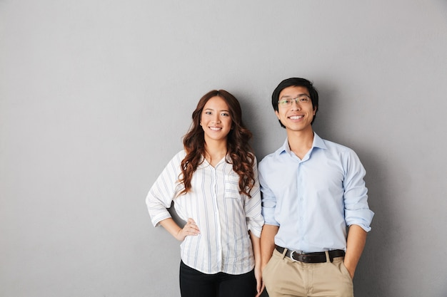 Cheerful asian business couple standing isolated