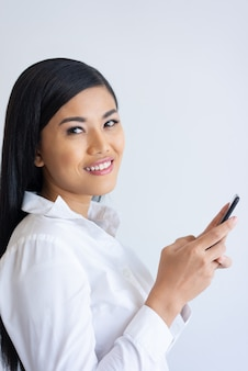 Cheerful asian business lady with black hair using smartphone