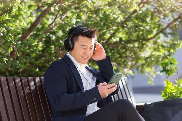 쾌활한 아시아 사업가는 시내 공원의 벤치에 앉아 손에 전화를 들고 헤드폰으로 음악을 듣고 있습니다. 정장을 입은 남성은 야외 활동을 즐깁니다. 긴장을 풀고 휴식을 취하십시오. 생활 양식