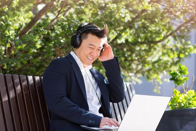ダウンタウンの都市公園のベンチに座って、ラップトップを使用してヘッドフォンで音楽を聴いている陽気なアジアのビジネスマン。スーツを着た男性がアウトドアを楽しんでいます。リラックスして休んでください。ライフスタイル