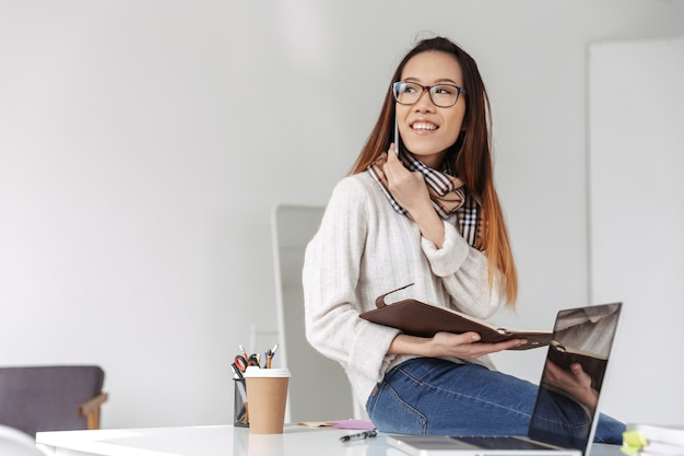 Cheerful asian business woman in eyeglasses talking by smartphone and looking away while holding folder with documents in office