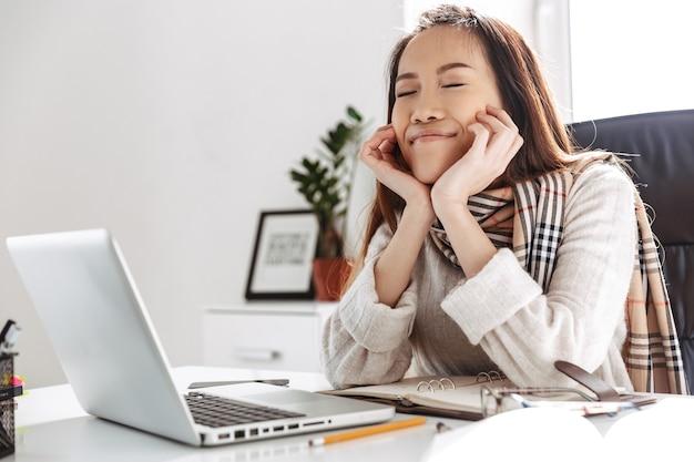 休憩し、オフィスのテーブルのそばに座って目を閉じて楽しむ陽気なアジアのビジネス女性