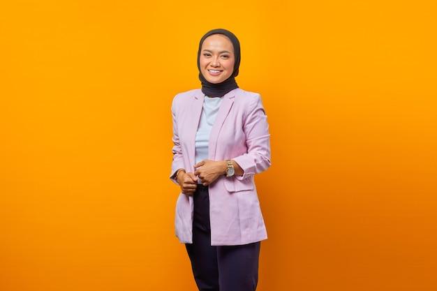 노란색 배경 위에 카메라를 보고 있는 쾌활한 아시아 비즈니스 여성