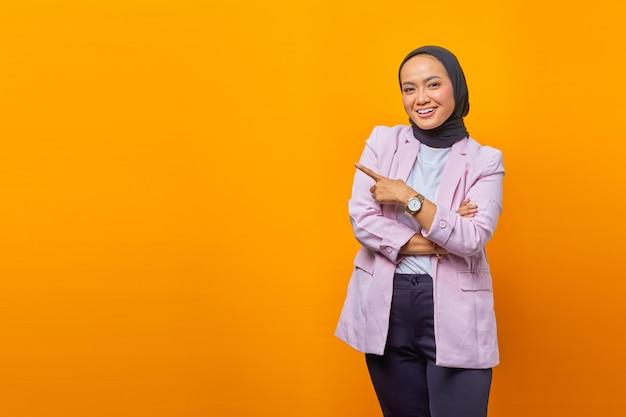 노란색 배경 위에 빈 공간을 가리키는 쾌활한 아시아 비즈니스 여성