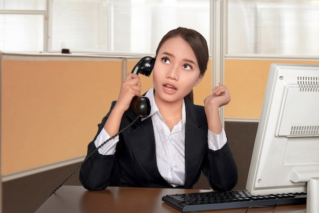 Cheerful asian business woman talking on the phone while sitting