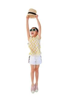 쾌활한 아시아 아이 선글라스를 착용하고 흰색에 밀짚 모자 점프를 들어 올려