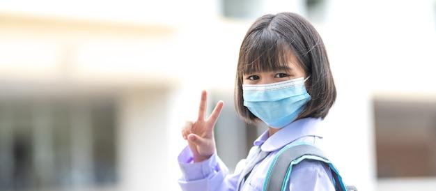 Веселые азиатские дети-ученики в школьной форме возвращаются в школу с медицинской маской для лица после пандемии covid-19. снова в школу stock photo
