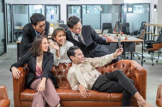 Веселые азиатские коллеги приветствуют селфи смартфоном на кожаном диване в коворкинге в современном офисе