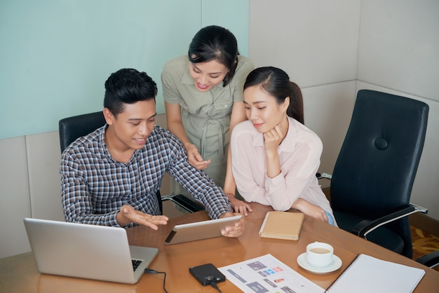 Cheerful asian colleagues sitting and standing around desk and looking at tablet together