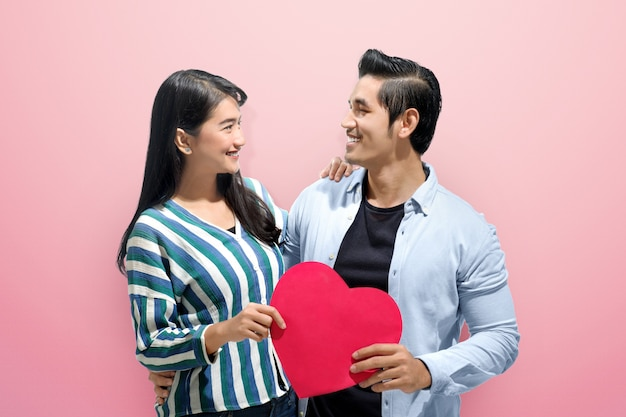 Cheerful asian couple embrace and holding red paper hearts