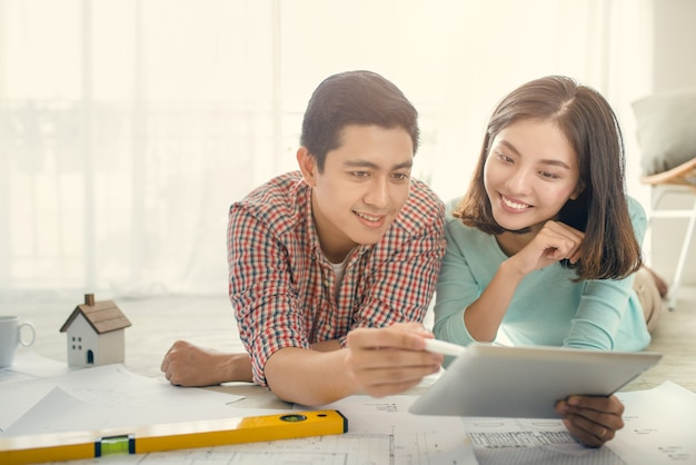 Веселая азиатская пара, глядя на план строительства дома