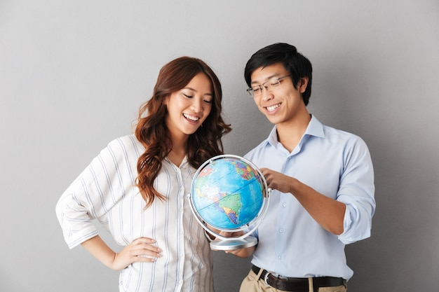 Веселая азиатская пара стоя изолированно, держа земной шар