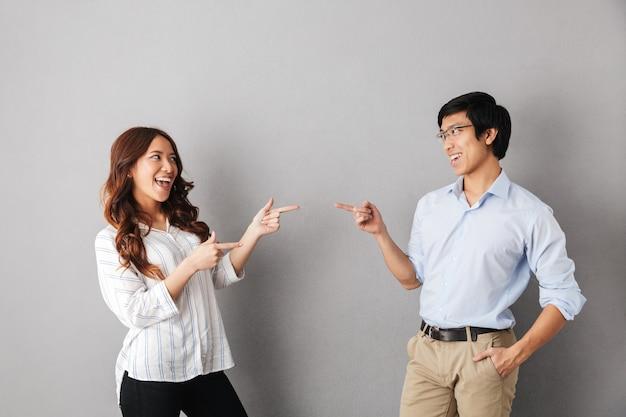 Веселая азиатская пара стоя изолированные, указывая