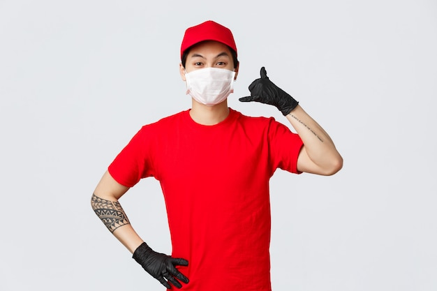 Cheerful asian delivery guy in medical mask and protective gloves show phone sign, asking clients give call anytime when delivery needed. charismatic courier promote fast shipment of parcel