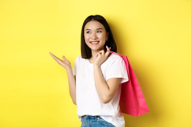 Cheerful asian female shopper looking amused, holding shopping bag and pointing hand left at store banner, standing over yellow background.